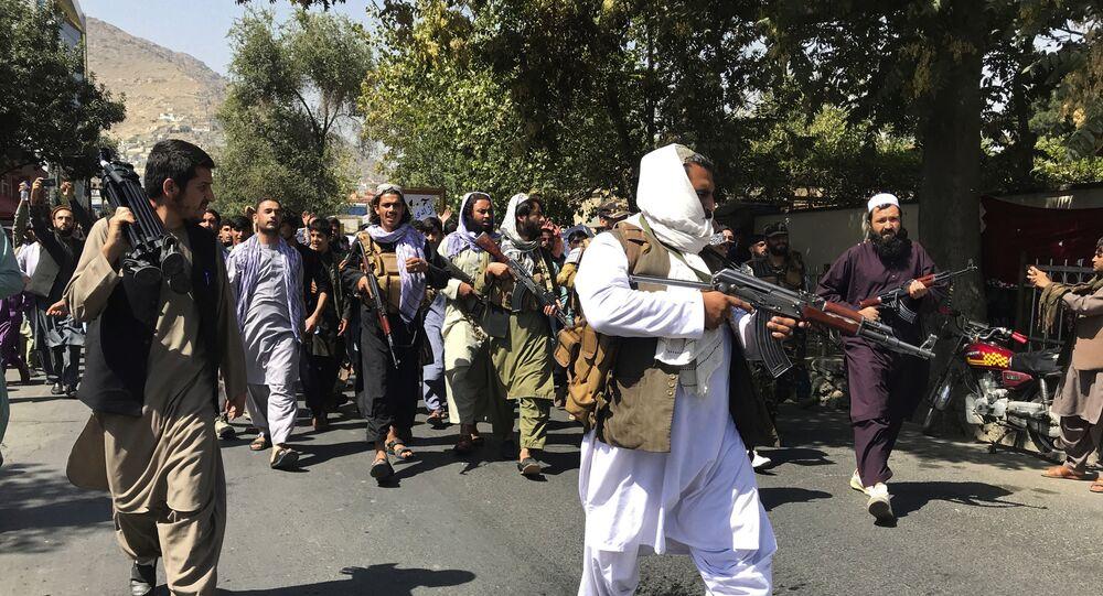 Soldados do Talibã andam em direção aos afegãos que protestam contra o Paquistão, 7 de setembro de 2021
