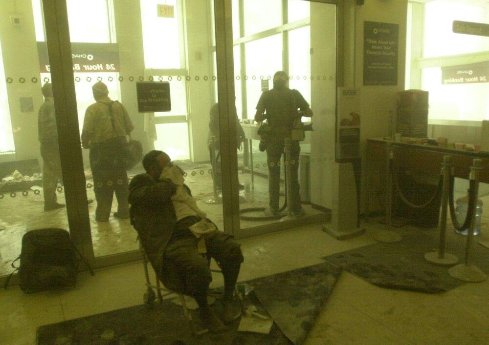 Homem ferido aguarda ajuda, enquanto outros se abrigam em um banco perto das torres do World Trade Center, 11 de setembro de 2001
