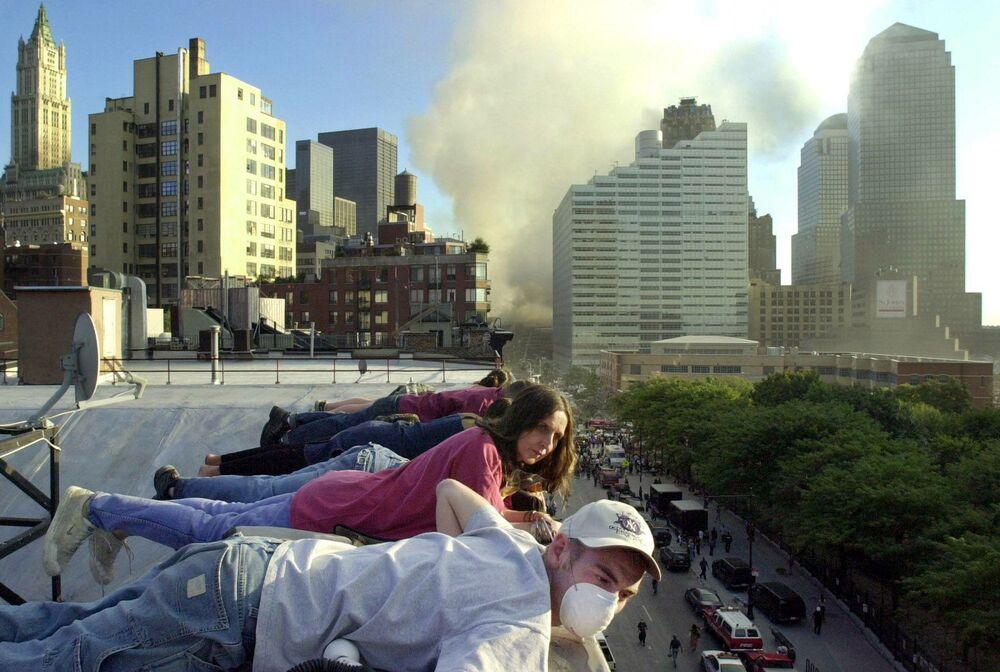 Pessoas no telhado de um prédio olham para a rua cheia de equipes de resgate, em meio à fumaça no local do ataque terrorista, Nova York, 12 de setembro de 2001