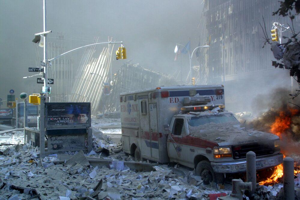 Ambulância, coberta com escombros, em chamas após o colapso da primeira Torre do World Trade Center, 11 de setembro de 2001