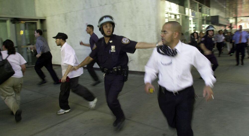 Pessoas correm enquanto o topo de uma das Torres Gêmeas desmorona após a colisão dos aviões sequestrados, 11 de setembro de 2001, Nova York