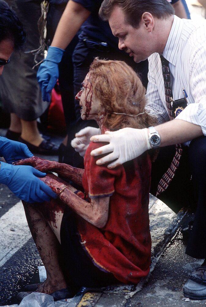 Trabalhadores de emergência ajudam uma mulher depois que ela ficou ferida no ataque terrorista ao World Trade Center em Nova York, 11 de setembro de 2001
