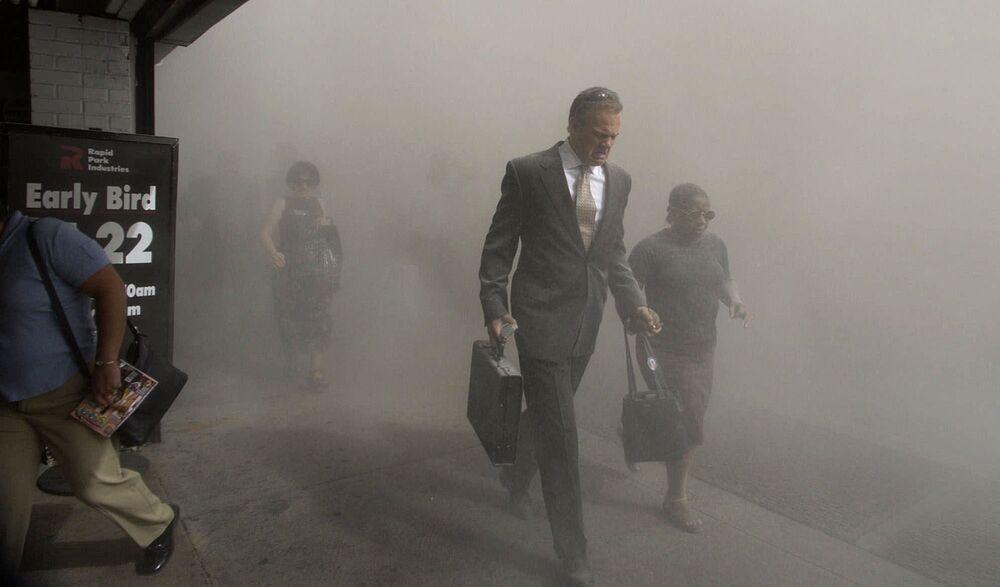 Pedestres fogem da área do World Trade Center desmoronado em Manhattan após os ataques terroristas em Nova York, 11 de setembro de 2001