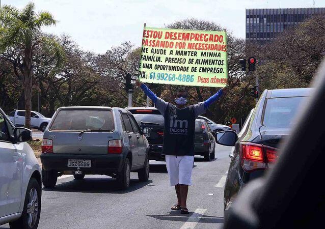 Homem segura cartaz pedindo emprego pelo trânsito do Distrito Federal. Segundo dados, o DF foi a unidade da federação que mais empobreceu entre o primeiro trimestre de 2019 e janeiro de 2021. 20 de agosto de 2021