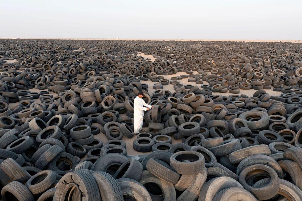 O sírio Ibrahim Kamal em pé entre pneus usados destinados à reciclagem no Kuwait, 4 de setembro de 2021