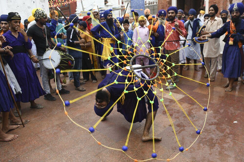 Jovem pratica arte marcial conhecida como Gatka no 417º aniversário do guru Granth Sahib, no Templo Dourado em Amritsar, 7 de setembro de 2021