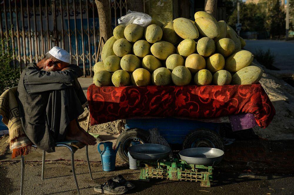 Afegão vendedor de frutas espera por clientes ao longo de rua em Cabul, 7 de setembro de 2021
