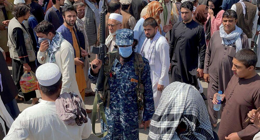 Um membro das forças de segurança do Talibã monta guarda entre as pessoas que passam em uma rua em Cabul, Afeganistão, 4 de setembro de 2021
