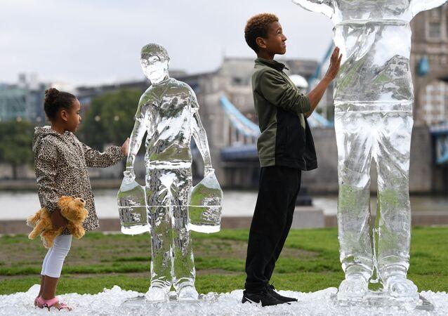 Crianças posam perto de esculturas de gelo representando pessoas coletando água da organização de caridade Water Aid, simbolizando a fragilidade da água e a ameaça das mudanças climáticas, Londres, 15 de setembro de 2021