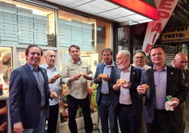 Presidente Jair Bolsonaro come pizza com integrantes do governo em rua de Nova York, EUA, antes da Assembleia Geral das Nações Unidas, em 19 de setembro de 2021. Foto tirada em 19 de setembro de 2021
