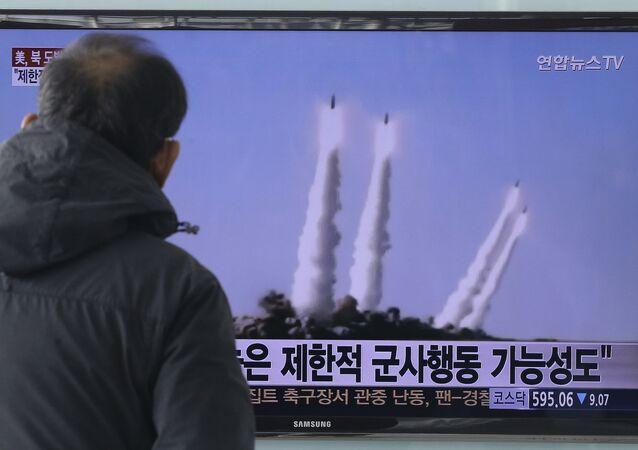 O homem na Coreia do Sul vê o lançamento de foguetes antinavios norte-coreanos