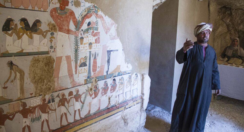 Um guarda egípcio ao lado de um mural fúnebre dentro de um túmulo recentemente descoberto, conhecido como KAMPP 161 durante um anúncio do Ministério das Antiguidades egípcio sobre novas descobertas em Luxor, no Egito.