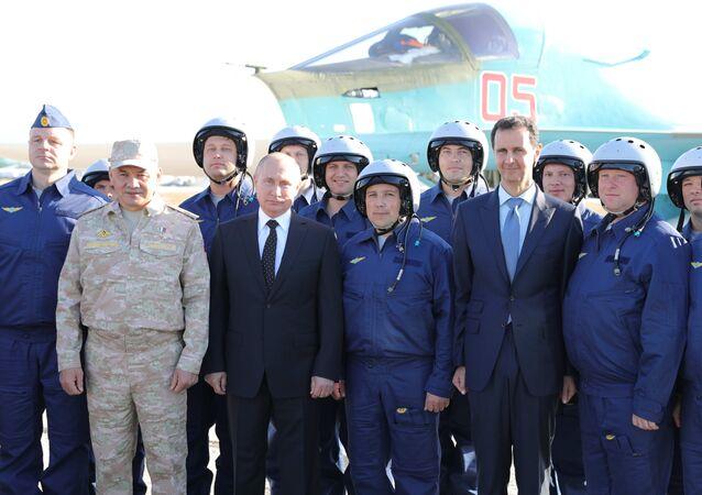 Presidente russo Vladimir Putin, ministro da Defesa russo Sergei Shoigu (E), presidente sírio Bashar Assad (D) e militares russos durante a visita de Putin à base aérea síria de Hmeymim