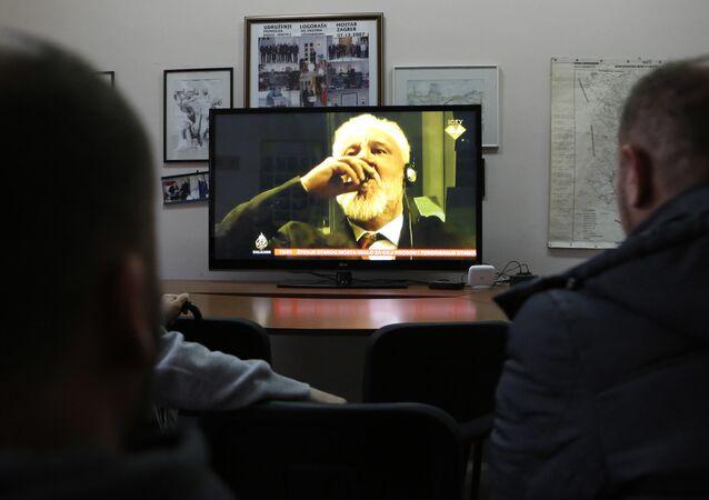 Slobodan Praljak, general croata da Bósnia e Herzegovina, sentenciado pelo Tribunal Penal Internacional a 20 anos de prisão, toma veneno em plena sala do tribunal após ouvir a sentença