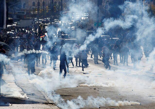 Manifestantes palestinos atacados com gás lacrimogêneo pelas tropas israelenses durante um protesto contra a decisão do presidente dos EUA, Donald Trump, de reconhecer Jerusalém como a capital de Israel, em 9 de dezembro de 2017