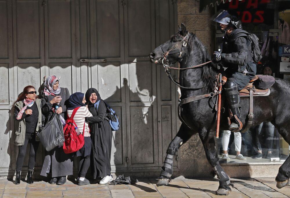 Mulheres assustadas com policial israelense que dispersa manifestantes palestinos em Jerusalém oriental