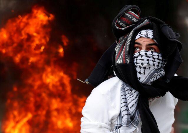 Um manifestante palestino atira uma pedra contra os soldados israelenses na Cisjordânia, em 20 de dezembro de 2017, durante os protestos populares contra a decisão de Donald Trump de reconhecer Jerusalém como a capital de Israel