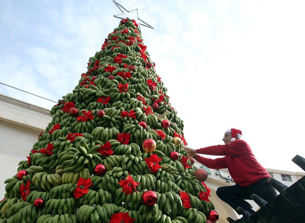 Homem adorna árvore de Natal feita de bananas na região de Damour, ao sul de Beirute, Líbano, em 19 de dezembro de 2017