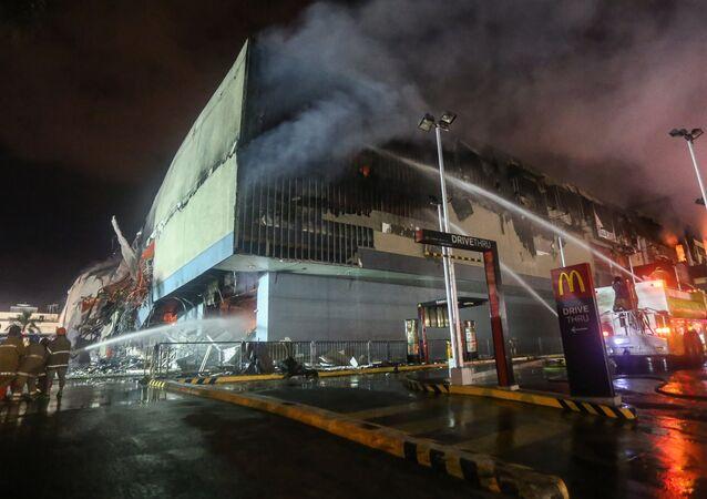 Bombeiros lutam para combater as chamas que atingiram um shopping na cidade de Davao, nas Filipinas
