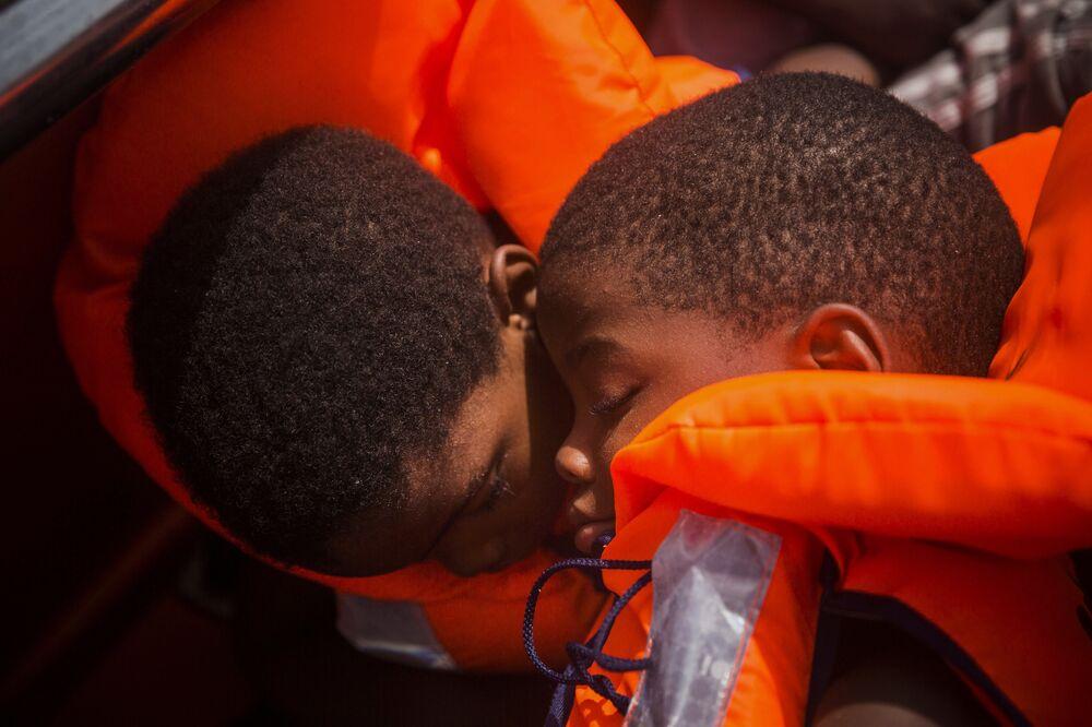 Dois migrantes em barco no Mar Mediterrâneo sendo resgatados. Milhares de refugiados e migrantes tentam chegar à Europa a partir da Líbia e morrem no caminho.