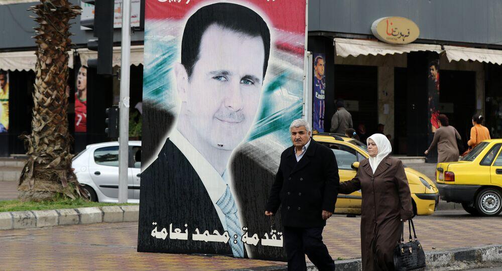 Sírios passeando perto do retrato do presidente do país, Bashar Assad