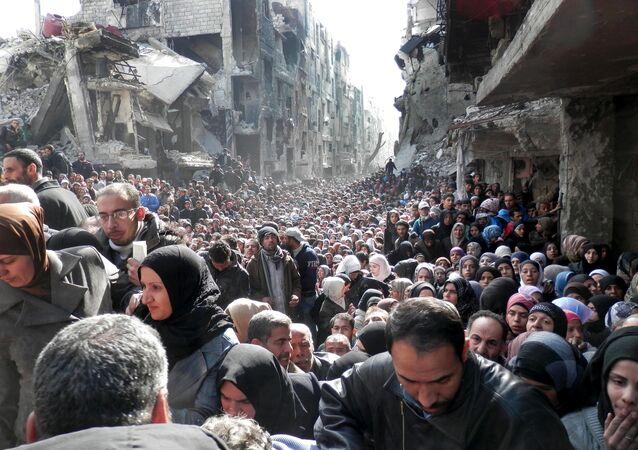Refugiados Palestinos do campo de Yarmouk, próximo a Damasco, na Síria, enquanto se organizam para retirar alimentos