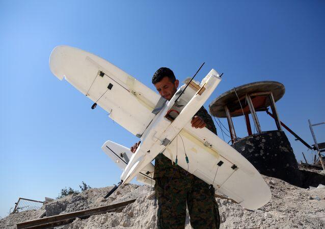 Membro das Forças Democráticas da Síria inspeciona drone derrubado alegadamente pertencente ao grupo terrorista Daesh (foto de arquivo)