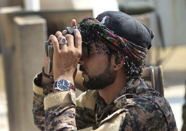 Combatente árabe com Forças Democráticas Sírias apoiadas pelos EUA olhando no binóculo em Raqqa, noroeste da Síria