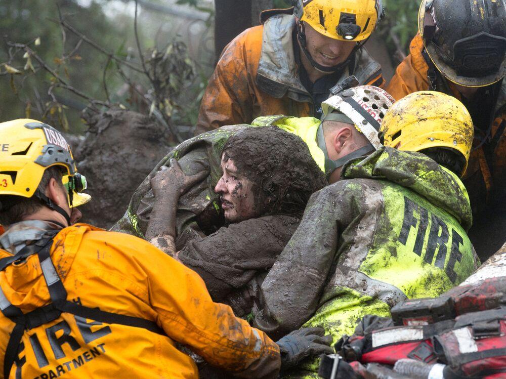 Socorristas resgatam mulher dos escombros de uma casa destruída por deslizamento de terra em Montecito, Califórnia, EUA