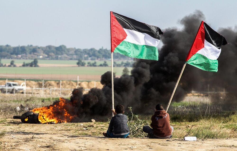Palestinos agitam bandeiras nacionais na fronteira entre Israel e Faixa de Gaza