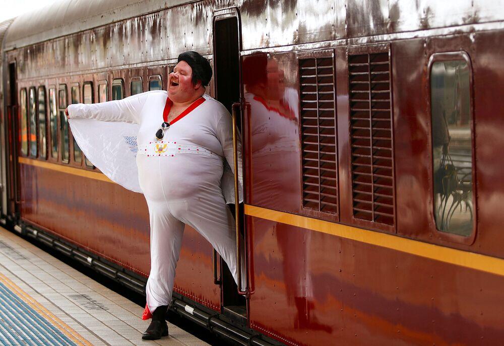 Sean Wright, vestido de Elvis Presley, desembarca do trem na Estação Central de Sydney, Austrália