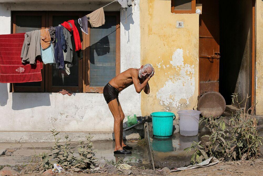 Homem toma banho no mercado na cidade indiana de Jammu