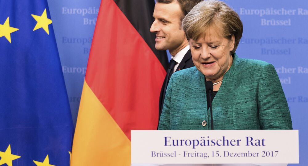French President Emmanuel Macron, left, passes by German Chancellor Angela Merkel prior to addressing a media conference at an EU summit in Brussels on Friday, Dec. 15, 2017.