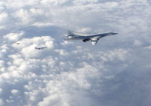 Dois bombardeiros de longo alcance russos Tu-160 são acompanhados por avião RAF Typhoon (à esquerda)