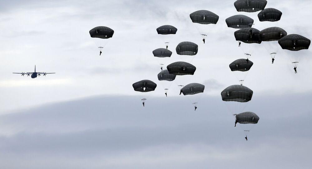 Soldados das tropas autotransportadas dos exércitos norte-americano e sérvio saltam do avião da Força Aérea dos EUA C-130 durante exercícios no aeroporto de Lisicji jarak, Sérvia