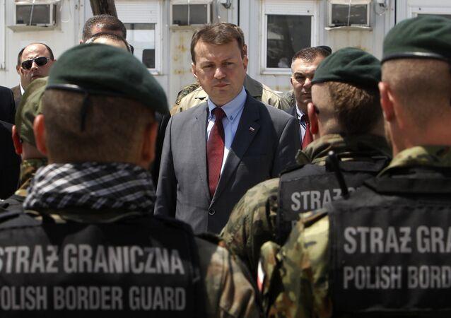 Mariusz Blaszczak, ministro do Interior da Polônia na época, fala com agentes da guarda de fronteira polonesa no centro de trânsito de refugiados perto da cidade macedônia de Gevgelija, em 24 de maio de 2016