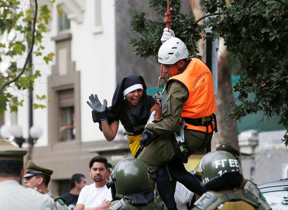 Polícia detém uma manifestante vestida de freira durante a visita do Papa Francisco à capital chilena, Santiago