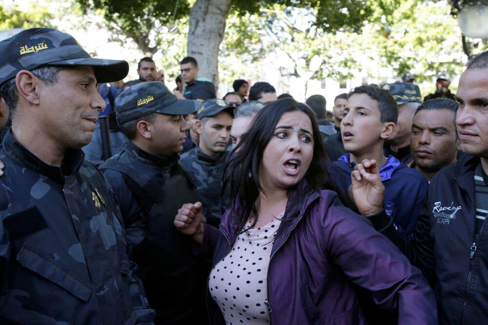 Mulher grita lemas durante as manifestações no 7º aniversário da derrubada do ex-presidente tunisiano, Zine El Abidine Ben Ali, em Tunes