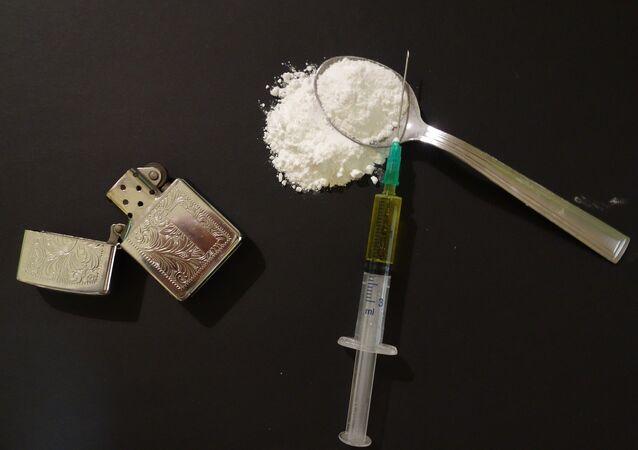 Heroína em uma colher, seringa e acendedor