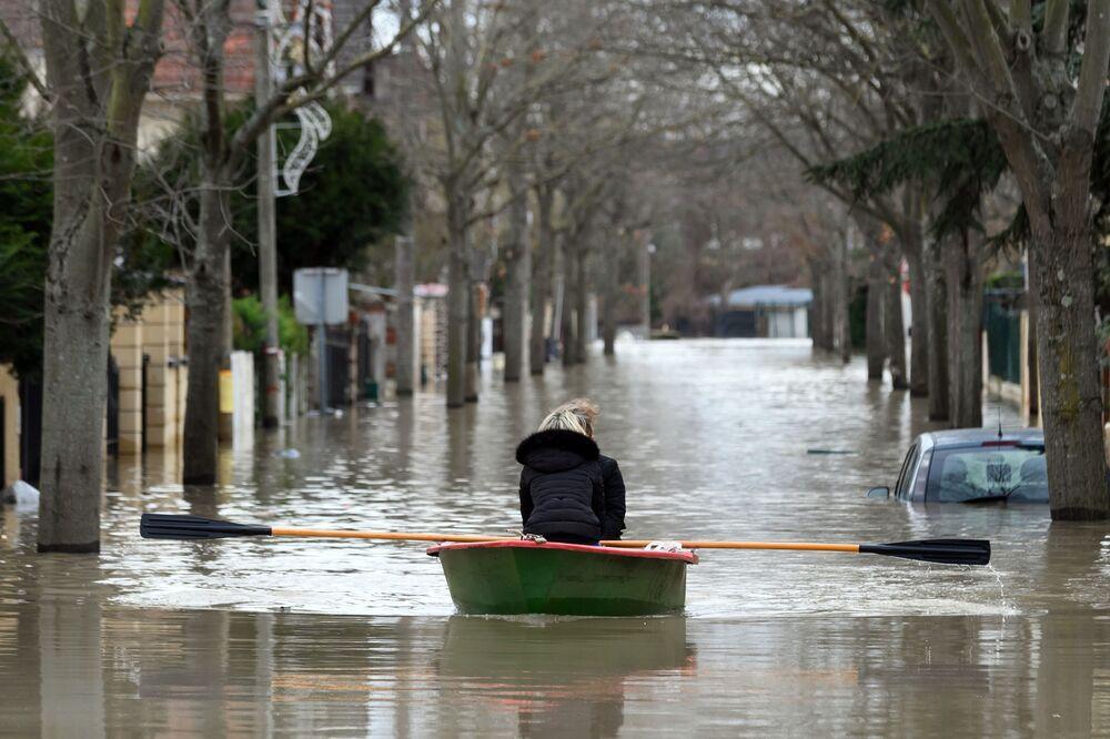 Residentes locais andam de barco em uma das ruas inundadas de Paris, após fortes aguaceiros na capital francesa