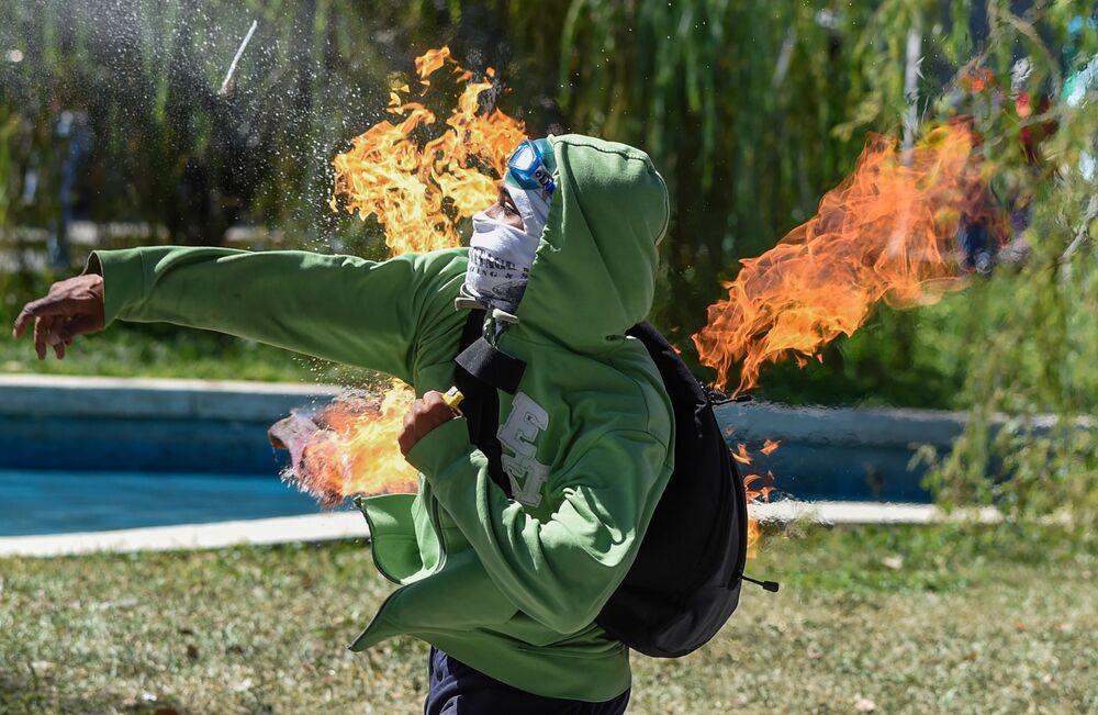 Manifestante lança um coquetel Molotov em um policial durante os confrontos em Caracas, na Venezuela