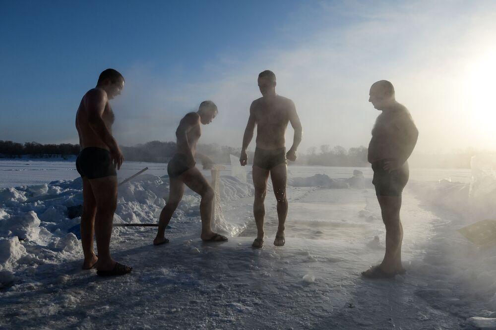 Entusiastas de natação de inverno durante mergulhos em abertura no gelo em um dos lagos congelados da região de Novosibirsk