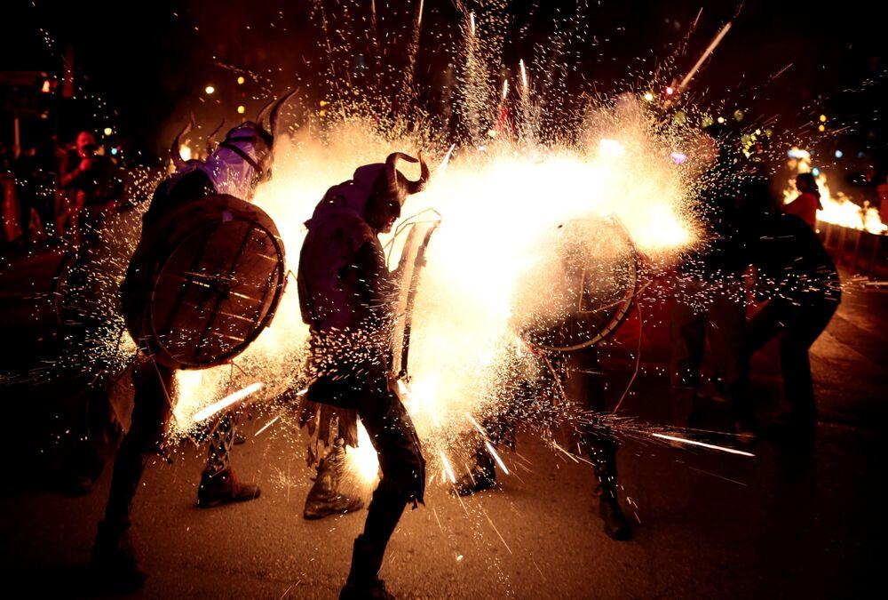 Participantes da marcha tradicional espanhola Correfocs, vestidos de diabos, festejam o evento em Palma de Mallorca, na Espanha