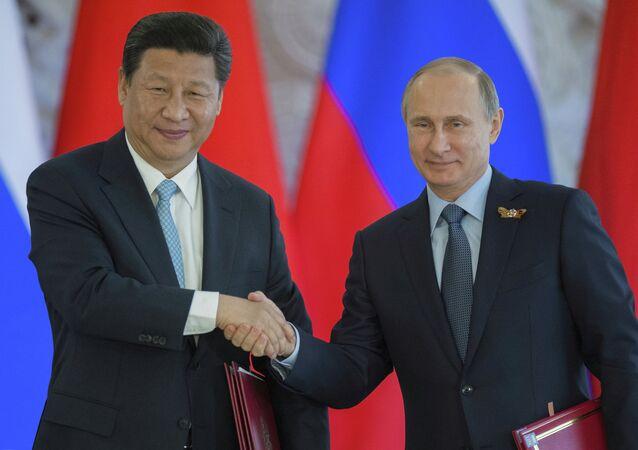 Vladimir Putin e Xi Junping após assinar um documento no Kremlin