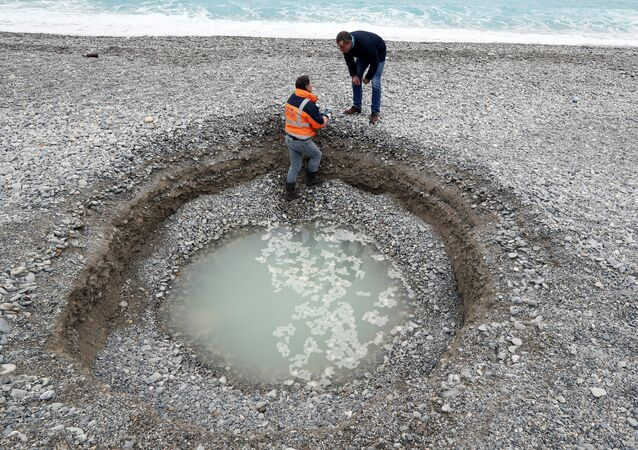 Um agente de obras municipais examina uma cratera de 2 metros de profundidade e 5 metros de largo  que se formou na cidade francesa de Nice em 1 de fevereiro de 2018