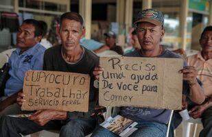 Migrantes venezuelanos seguram cartazes à procura de ajuda na cidade brasileira de Boa Vista, estado de Roraima (arquivo)