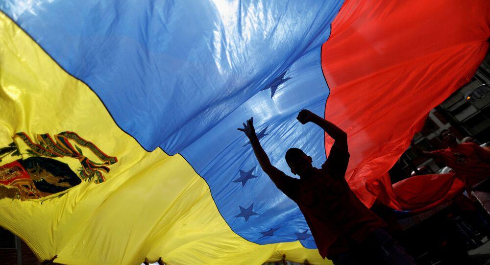 Manifestantes tremulam um bandeirão da Venezuela em manifestação contra o presidente dos EUA, Donald Trump, em Caracas, Venezuela (agosto de 2017)