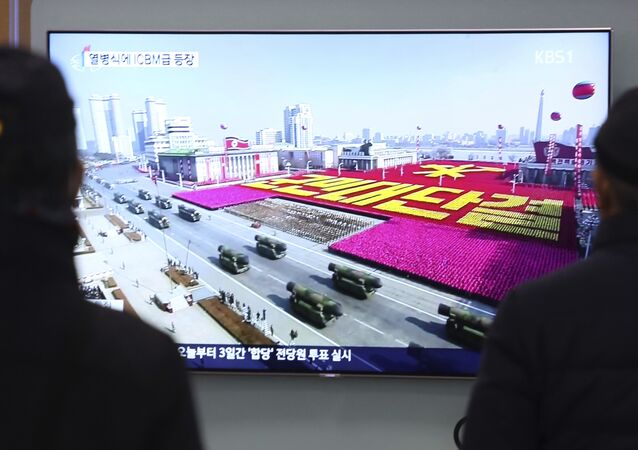 Pessoas assistem à transmissão do desfile militar em Pyongyang, Coreia do Norte, ocorrido em 8 de fevereiro de 2018
