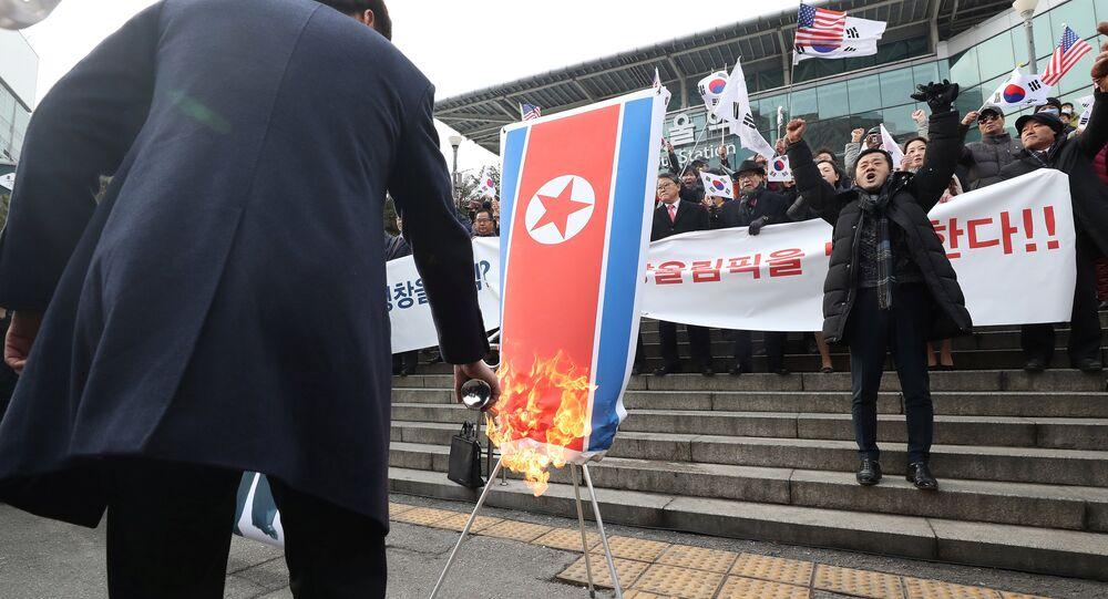 Membro do grupo civil sul-coreano queimando a bandeira nacional da Coreia do Norte durante a manifestação contra participação de Pyongyang nos Jogos Olímpicos em PyeongChang