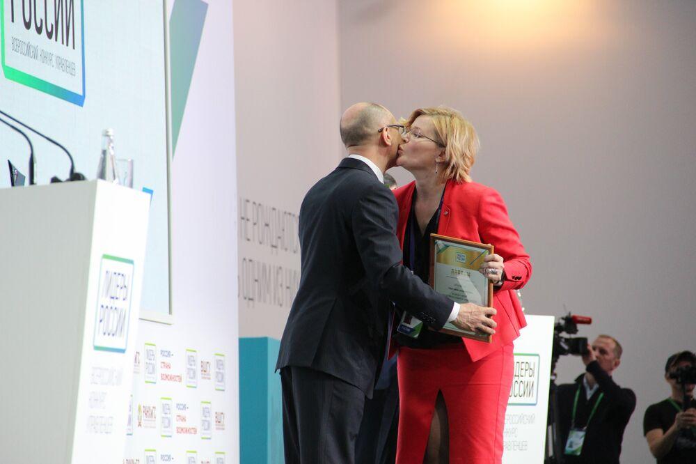 Alena Geidt, empresária do banco VTB no Cazaquistão, beija Sergei Kirienko, primeiro vice-chefe da administração da Presidência da Rússia, ao receber o prêmio